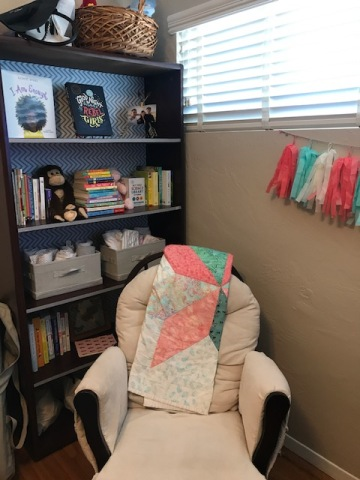 nursery rocking chair with bookshelves filled with baby items and books