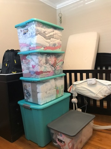stack of bins filled with baby gear